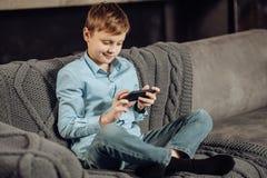 Muchacho agradable que se sienta en el sofá y que juega en el teléfono Fotos de archivo libres de regalías