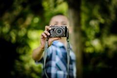 Muchacho al aire libre que sostiene la pequeña cámara Imagen de archivo