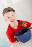 Muchacho al lado del bol grande y de la espátula con el chocolate Imagen de archivo