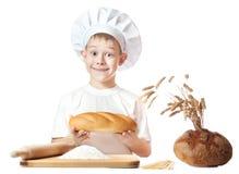 Muchacho alegre del panadero con una barra de pan Imagen de archivo libre de regalías