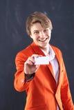 Muchacho alegre en chaqueta anaranjada con el escaparate blanco Fotos de archivo