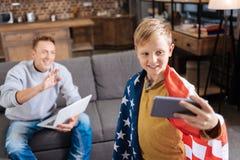 Muchacho alegre en la bandera de los E.E.U.U. que toma el selfie con su padre Foto de archivo libre de regalías