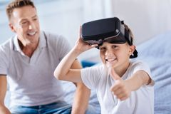 Muchacho alegre en las auriculares de VR que muestran los pulgares para arriba Imagen de archivo