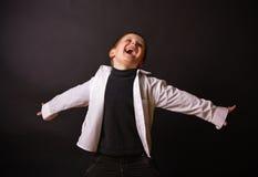 Muchacho alegre en un fondo negro Foto de archivo libre de regalías