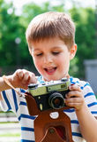 Muchacho alegre feliz con una cámara, el bebé fotografiado al aire libre Imagenes de archivo
