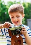 Muchacho alegre feliz con una cámara, el bebé fotografiado al aire libre Fotografía de archivo libre de regalías