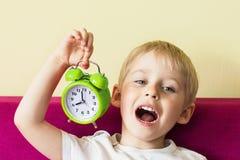 Muchacho alegre feliz que sostiene un despertador, rojo del despertador del bebé Fotografía de archivo libre de regalías