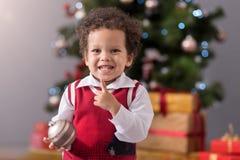 Muchacho alegre lindo que sostiene una decoración del árbol de navidad foto de archivo