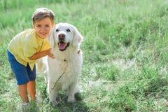 Muchacho alegre que abraza su perro en campo de hierba Foto de archivo