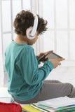 Muchacho alegre que escucha la música con los libros Foto de archivo libre de regalías