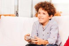 Muchacho alegre que juega al juego de la consola después de escuela imagen de archivo libre de regalías