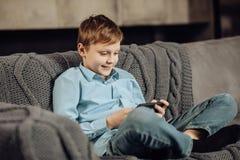 Muchacho alegre que juega en el teléfono mientras que se sienta en el sofá Imágenes de archivo libres de regalías