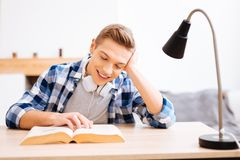 Muchacho alegre que lee un libro en la tabla Imagen de archivo libre de regalías