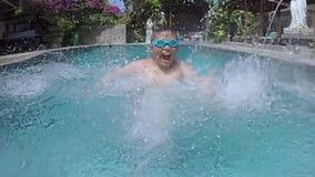 Muchacho alegre que salpica el agua en piscina