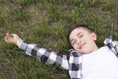 Muchacho alegre que se relaja en hierba verde Fotografía de archivo libre de regalías
