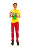 Muchacho alegre que sostiene el cubo con los tulipanes rosados Fotografía de archivo