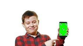 Muchacho alegre que sostiene un smartphone en su mano con una pantalla verde y demostraciones un finger en la pantalla metrajes