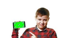 Muchacho alegre que sostiene un smartphone en su mano con una pantalla verde y demostraciones un finger en la pantalla almacen de video