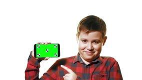 Muchacho alegre que sostiene un smartphone en su mano con una pantalla verde y demostraciones un finger en la pantalla almacen de metraje de vídeo