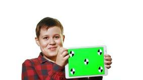 Muchacho alegre que sostiene una tableta en su mano con una pantalla verde almacen de metraje de vídeo