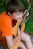 Muchacho alegre que toca la guitarra Imagenes de archivo