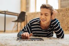 Muchacho alegre que trabaja en la tableta mientras que miente en el piso Fotografía de archivo