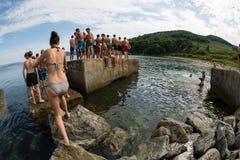Muchacho alegre y muchacha que saltan en el mar del embarcadero viejo Foto de archivo libre de regalías