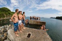 Muchacho alegre y muchacha que saltan en el mar del embarcadero viejo Foto de archivo