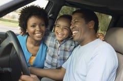 Muchacho alegre y padres que se sientan en coche Imágenes de archivo libres de regalías