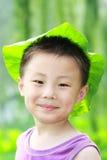 Muchacho asiático con el casquillo de la hoja Foto de archivo