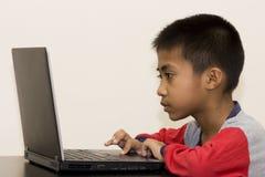 Muchacho asiático con la computadora portátil Fotos de archivo libres de regalías