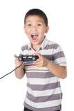Muchacho asiático con una palanca de mando que juega a los videojuegos, aislados en blanco Foto de archivo libre de regalías