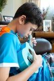 Muchacho asiático de la cacerola joven que practica en su ukelele azul en una ambiente familiar Fotografía de archivo libre de regalías