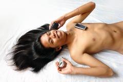 Muchacho asiático de pelo largo con 3 teléfonos celulares. Foto de archivo