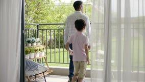 Muchacho asiático después del padre que sale al balcón almacen de video