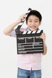 Muchacho asiático feliz que lleva a cabo el tablero de chapaleta en manos Concepto del cine Imagen de archivo