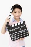 Muchacho asiático feliz que lleva a cabo el tablero de chapaleta en manos Concepto del cine Imágenes de archivo libres de regalías