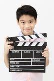 Muchacho asiático feliz que lleva a cabo el tablero de chapaleta en manos Concepto del cine Fotografía de archivo