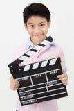 Muchacho asiático feliz que lleva a cabo el tablero de chapaleta en manos Concepto del cine Foto de archivo libre de regalías