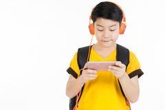 Muchacho asiático feliz que usa el teléfono celular Imágenes de archivo libres de regalías
