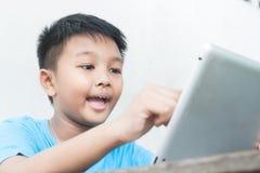 Muchacho asiático feliz que usa la tableta, niño que usa el ordenador y la tecnología fotografía de archivo libre de regalías