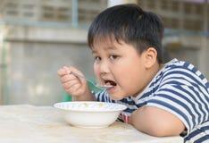 Muchacho asiático gordo que come las avenas con leche Foto de archivo libre de regalías