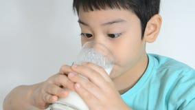 Muchacho asiático joven que bebe un vidrio de leche almacen de metraje de vídeo