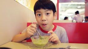 Muchacho asiático joven que come un helado en la taza, cara feliz almacen de video