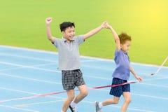 Muchacho asiático joven que corre en pista azul en el estadio Fotografía de archivo libre de regalías