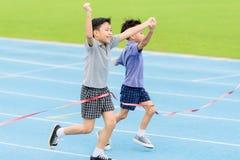 Muchacho asiático joven que corre en pista azul en el estadio Foto de archivo