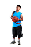 Muchacho asiático joven que se coloca con baloncesto Fotos de archivo