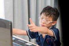 Muchacho asiático joven que usa el ordenador portátil Imagenes de archivo