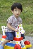 Muchacho asiático lindo en un caballo del juguete Imagen de archivo libre de regalías