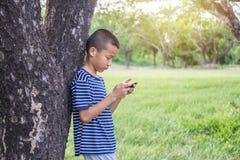 Muchacho asiático lindo joven que usa un smartphone Fotos de archivo libres de regalías